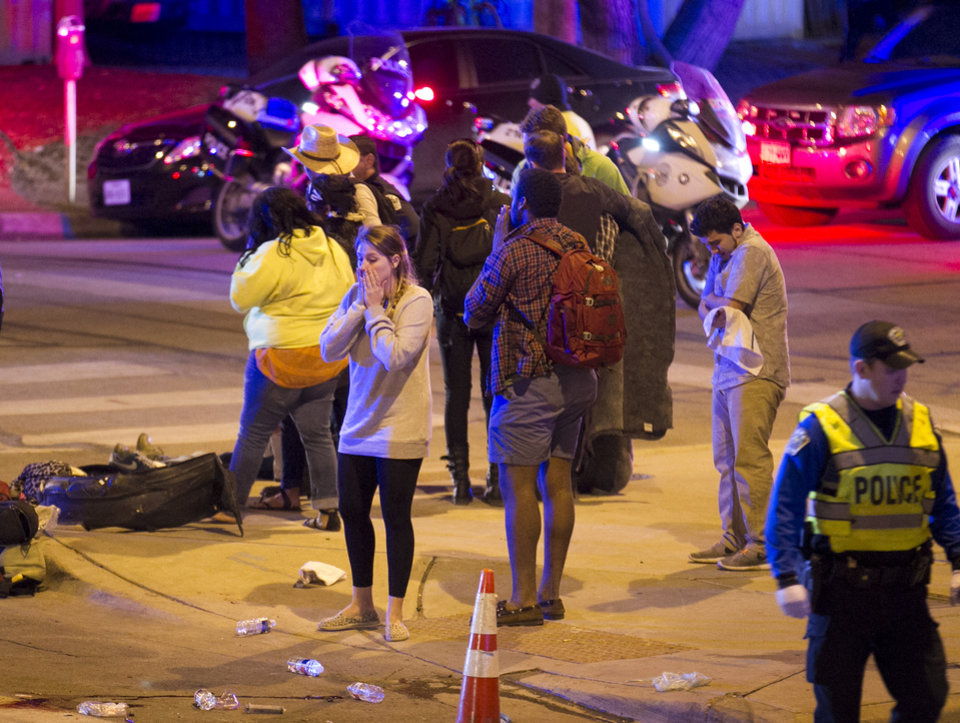 Photo - Bystanders react after several people were struck by a vehicle on Red River Street in downtown Austin, Texas, at SXSW on Wednesday March 12, 2014. Police say two people were confirmed dead at the scene after a car drove through temporary barricades set up for the South By Southwest festival and struck a crowd of pedestrians.  (AP Photo/Austin American-Statesman, Jay Janner)