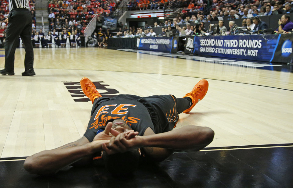Photo - Oklahoma State's Marcus Smart (33) lays on the floor after a foul during a second round game of the NCAA men's college basketball tournament at Viejas Arena in San Diego, between Oklahoma State and Gonzaga Friday, March 21, 2014. Gonzaga won 85-77. Photo by Bryan Terry, The Oklahoman