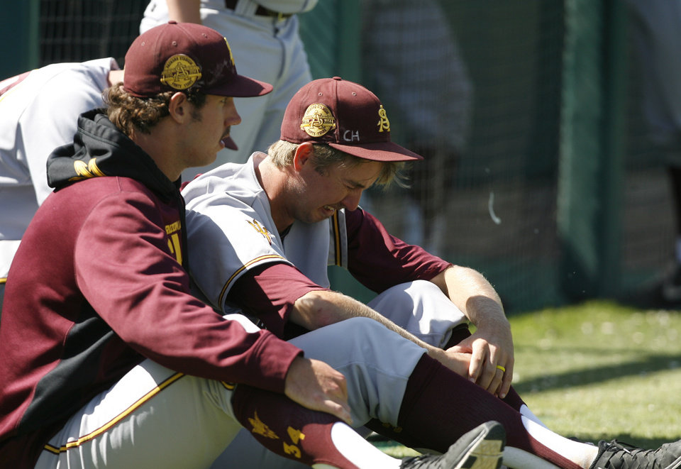 Photo - Arizona State's Josh McAlister, right, is consoled by a teammate following their loss to Sacramento State in an NCAA college baseball tournament regional game on Saturday, May 31, 2014, in San Luis Obispo, Calif. (AP Photo/Aaron Lambert)