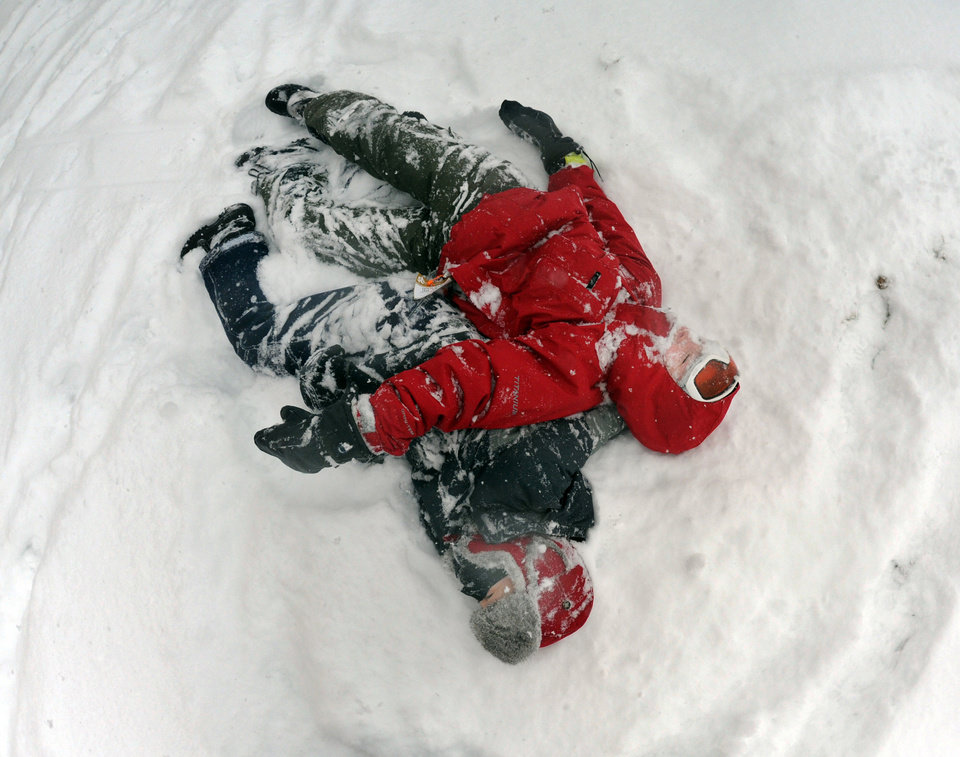 Photo - Dyloan Witzig, right, and his brother Zach, catch their breath after wrestling on the hill behind York Suburban High School on Tuesday,  Jan. 21, 2014, in York, Pa. The National Weather Service predicts the storm could drop 8 to 12 inches of snow followed by bitterly cold temperatures. (AP Photo/York Daily Record, Jason Plotkin)  YORK DISPATCH OUT