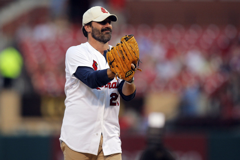 Photo - Actor and St. Louis native Jon Hamm throws out a ceremonial first pitch prior to a baseball game between the St. Louis Cardinals and the Cincinnati Reds, Monday, Aug. 18, 2014, in St. Louis. Hamm is being honored tonight by the Cardinals with a give-away promotion, and portions of proceeds from the purchase of promotional tickets being donated to St. Jude Children's Medical Research Hospital in his honor. (AP Photo/Scott Kane)