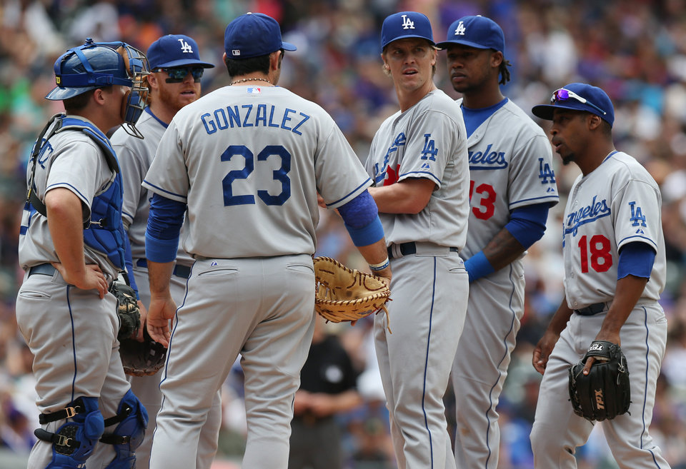Photo - Los Angeles Dodgers starting pitcher Zack Greinke,  third from right, confers with, from left, catcher Tim Federowicz, third baseman Justin Turner, first baseman Adrian Gonzalez, shortstop Hanley Ramirez and second baseman Chone Figgins after giving up an RBI-single to Colorado Rockies' Josh Rutledge in the fifth inning of a baseball game in Denver on Saturday, June 7, 2014. (AP Photo/David Zalubowski)
