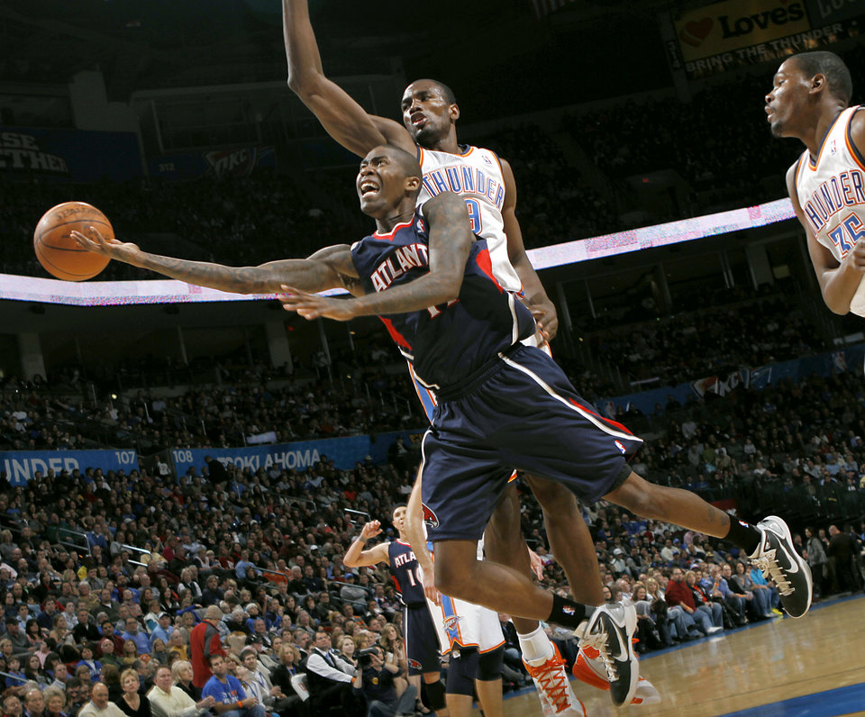 Photo - Oklahoma City's Serge Ibaka and Kevin Durant (right) pressure a shot by Atlanta's Jamal Crawford during their NBA basketball game at the OKC Arena in Oklahoma City on Friday, Dec. 31, 2010. The Thunder beat the Hawks 103-94. Photo by John Clanton, The Oklahoman