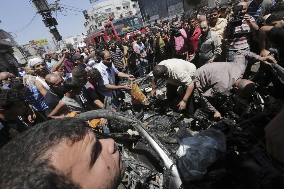 Photo - Palestinians search the wreckage of a vehicle following an Israeli air strike on it at the main road in Gaza City, in the northern Gaza Strip, Tuesday, July 8, 2014. The Israeli military launched what could be a long-term offensive against the Hamas-ruled Gaza Strip on Tuesday striking nearly 100 sites in Gaza and mobilizing troops for a possible ground invasion aimed at stopping a heavy barrage of rocket attacks against Israel.(AP Photo/Adel Hana)