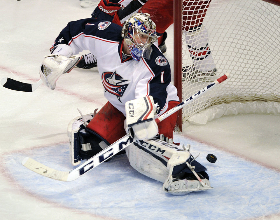 Photo - Columbus Blue Jackets' Steve Mason (1) watches the shot of the Chicago Blackhawks' Andrew Shaw dribble slide past him for a goal during the second period of an NHL hockey game Sunday, Feb. 24, 2013, in Chicago. (AP Photo/Jim Prisching)
