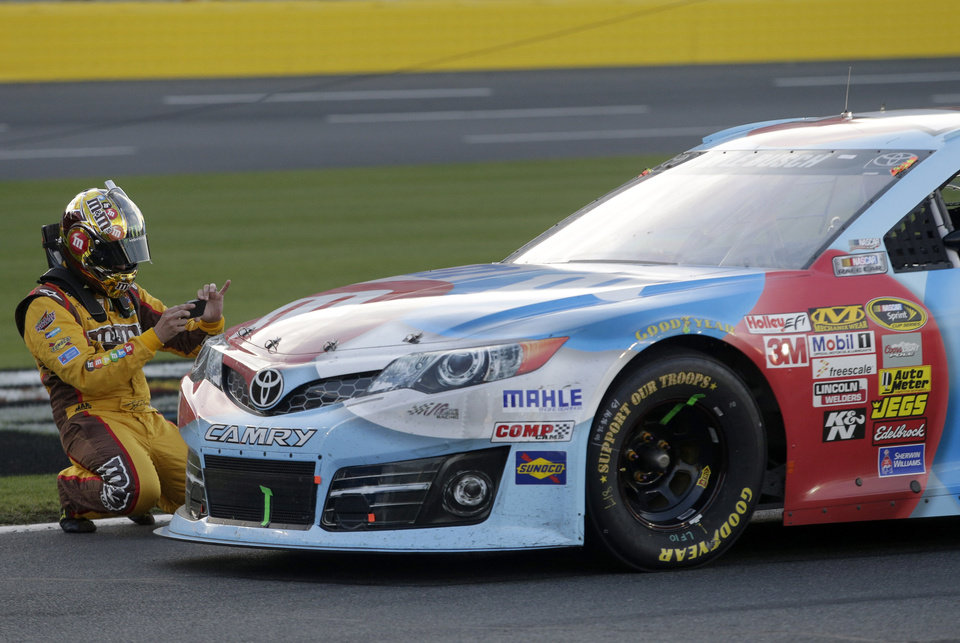 Kyle Busch takes a photo of his damaged race car with his phone camera during a red flag in the NASCAR Sprint Cup series Coca-Cola 600 auto race at Charlotte Motor Speedway in Concord, N.C., Sunday, May 26, 2013. (AP Photo/Nell Redmond)