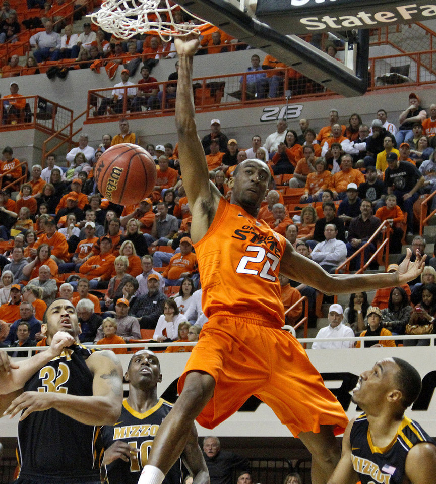 Photo - Oklahoma State's Markel Brown (22) dunks the ball over Missouri's Steve Moore (32), Ricardo Ratliffe (10), and Matt Pressey (3) during an NCAA college basketball game between the Oklahoma State University Cowboys (OSU) and the Missouri Tigers (MU) at Gallagher-Iba Arena in Stillwater, Okla., Wednesday, Jan. 25, 2012. Photo by Bryan Terry, The Oklahoman