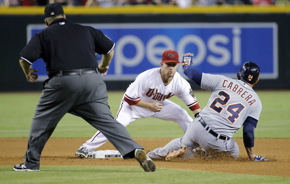 Photo - Detroit Tigers' Miguel Cabrera (24) is tagged out trying to advance to second after hitting an RBI single as Arizona Diamondbacks' Aaron Hill applies the tag during the sixth inning of a baseball game, Monday, July 21, 2014, in Phoenix.  (AP Photo/Matt York)