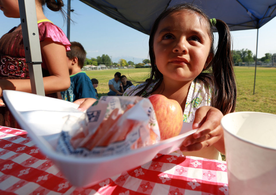 Photo -       Jasmine Alfaro gets dinner outside of the Central Park Community Center in South Salt Lake on Friday, July 18, 2014. The dinner is part of the Salt Lake CAP summer food program, which offers free dinner to children at five locations in the valley, Monday through Friday.
