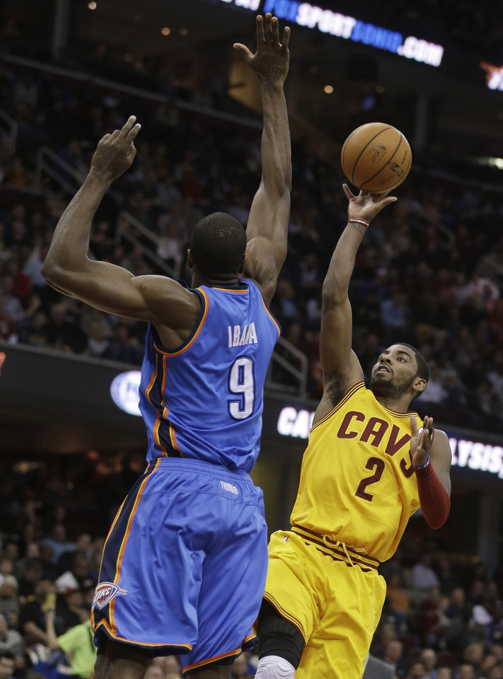 Photo - Cleveland Cavaliers' Kyrie Irving (2) shoots over Oklahoma City Thunder's Serge Ibaka (9), from the Republic of Congo, during the second quarter of an NBA basketball game on Saturday, Feb. 2, 2013, in Cleveland. (AP Photo/Tony Dejak) ORG XMIT: OHTD105