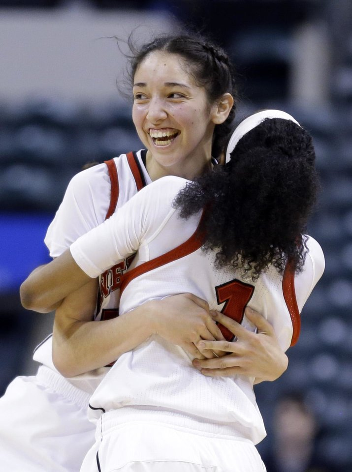 Photo - Nebraska forward Jordan Hooper, left, hugs guard Tear'a Laudermill after they defeated Iowa in an NCAA college basketball game in the finals of the Big Ten women's tournament in Indianapolis, Sunday, March 9, 2014. Nebraska won 72-65. (AP Photo/Michael Conroy)