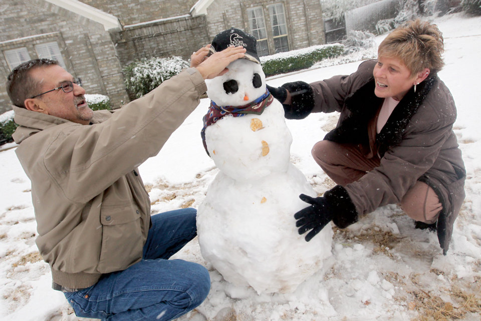 Tommy and Cindy Huddleston put the finishing touches on their snowman in Paris, Texas Tuesday, Dec. 25, 2012 after a strong winter system dropped inches of rain and snow on most of North East Texas. (AP Photo/The Paris News, Sam Craft)