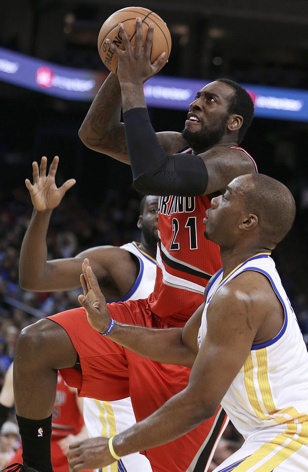 Photo - Portland Trail Blazers' J.J. Hickson (21) shoots over Golden State Warriors' Carl Landry during the first half of an NBA basketball game Friday, Jan. 11, 2013, in Oakland, Calif. (AP Photo/Ben Margot)