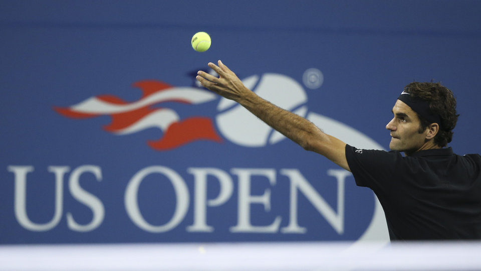 Photo - Roger Federer, of Switzerland, serves to Gael Monfils, of France, during the quarterfinals of the U.S. Open tennis tournament, Thursday, Sept. 4, 2014, in New York. (AP Photo/John Minchillo)