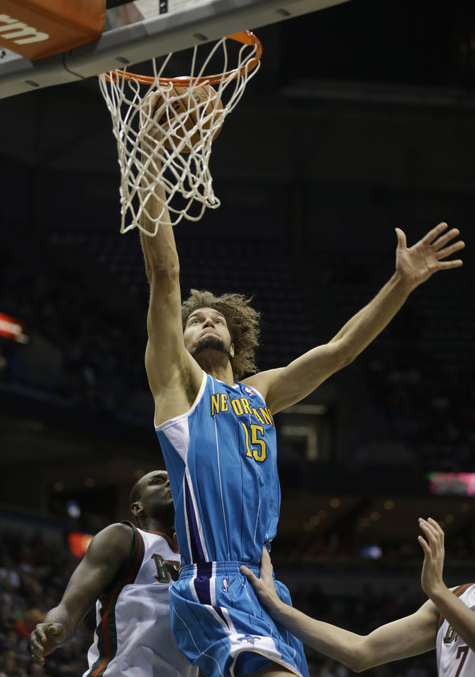 New Orleans Hornets' Robin Lopez puts up a shot against Milwaukee Bucks' Samuel Dalembert during the first half of an NBA basketball game Saturday, Nov. 17, 2012, in Milwaukee. (AP Photo/Jeffrey Phelps)
