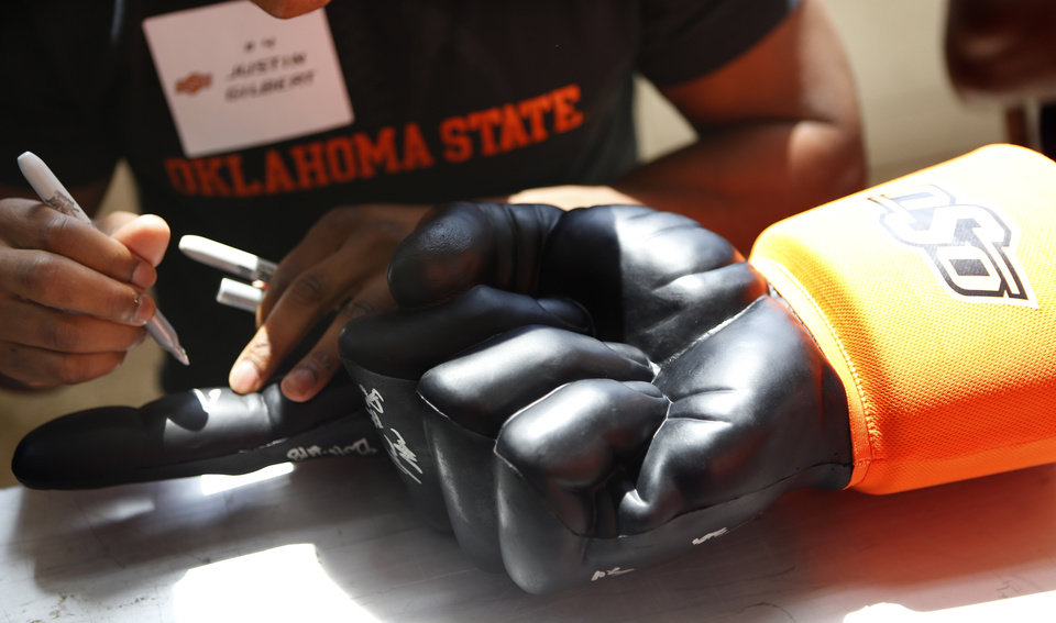 Photo - Oklahoma State football player Justin Gilbert signs an autograph during Oklahoma State's Fan Appreciation Day at Gallagher-Iba Arena in Stillwater, Okla., Saturday, Aug. 4, 2012. Photo by Sarah Phipps, The Oklahoman