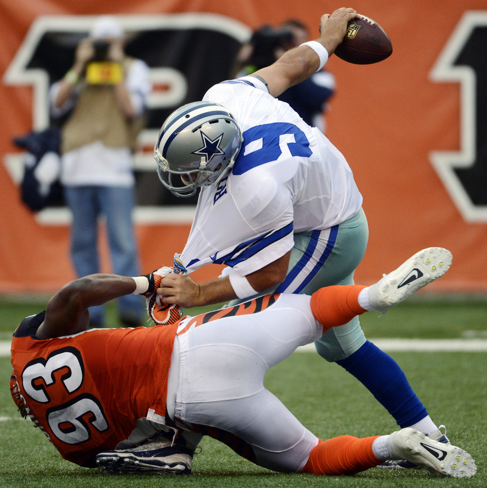 Photo - Dallas Cowboys quarterback Tony Romo (9) is sacked by Cincinnati Bengals defensive end Michael Johnson (93) in the first half of an NFL football game, Sunday, Dec. 9, 2012, in Cincinnati. (AP Photo/Michael Keating)