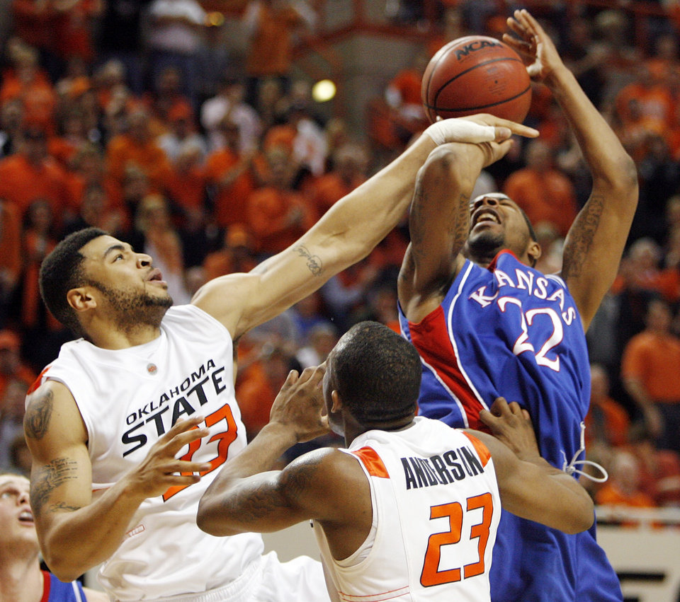 Photo - OSU's Marshall Moses (23) fouls Marcus Morris (22) of KU in front of OSU's James Anderson (23) during the second half during the men's college basketball game between the University of Kansas (KU) and Oklahoma State University (OSU) at Gallagher-Iba Arena in Stillwater, Okla., Saturday, Feb. 27, 2010. OSU won, 85-77. Photo by Nate Billings, The Oklahoman