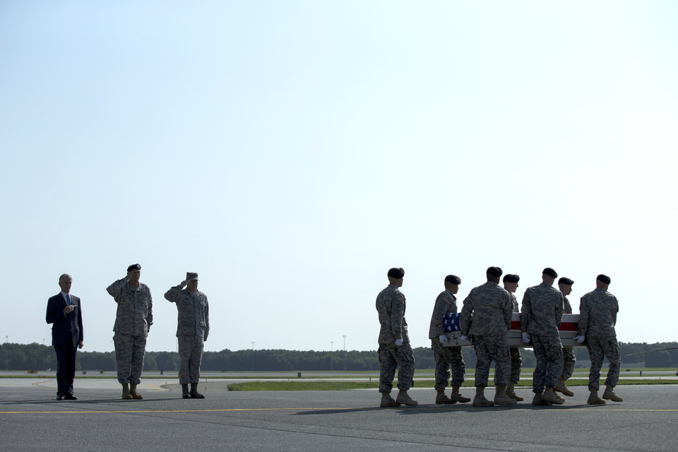 Photo - Army Secretary John McHugh, left, and Army Chief of Staff Ray Odierno, second from left, watch as an Army carry team transfers the remains of Army Maj. Gen. Harold Greene at Dover Air Force Base, Del., Thursday, Aug. 7, 2014.  Greene was shot to death Tuesday when a gunman dressed as an Afghan soldier turned on ISAF troops, wounding about 15 including a German general and two Afghan generals. He is the highest-ranking U.S. military officer to be killed in either of America's post-9/11 wars. (AP Photo/Evan Vucci)