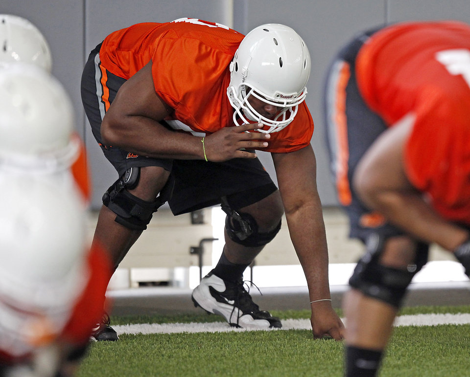 Photo - Oklahoma State offensive lineman Devin Davis (69) lines up during the first team practice of the fall at the Sherman E. Smith Training Facility on the campus of Oklahoma State University in Stillwater on August 1, 2014. Photo by KT King, The Oklahoman