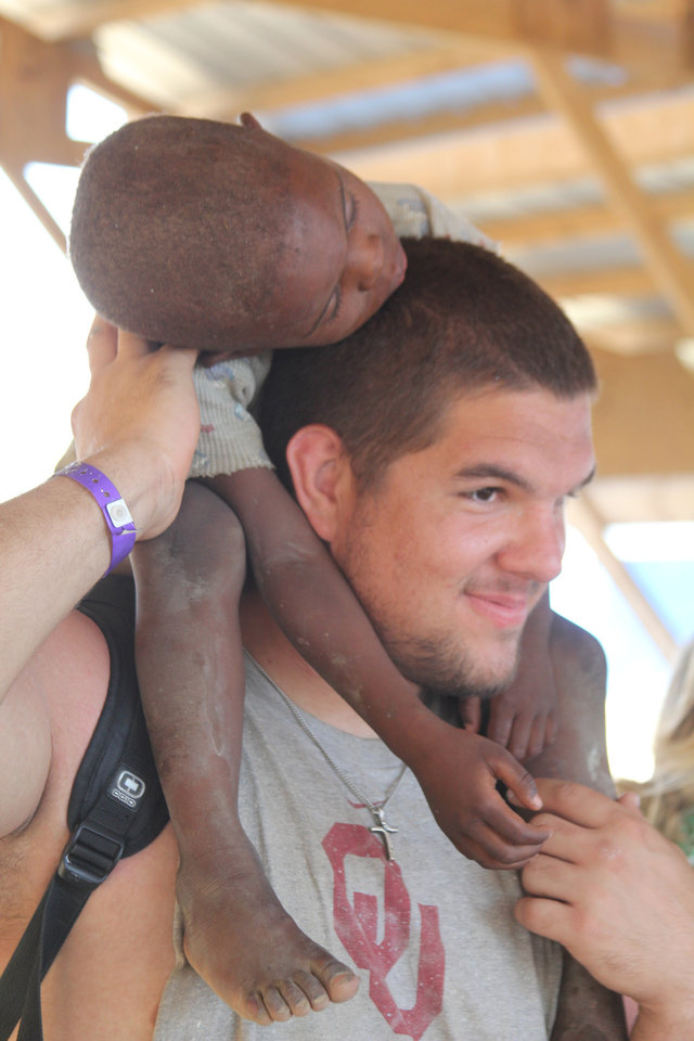 Photo - OU offensive lineman Ben Habern holds DeSong above his head on a recent trip to Haiti. Photo by Michael Davis.