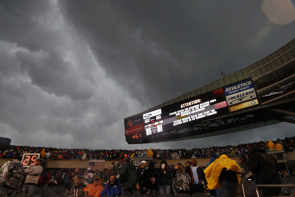 Photo - Fans are advised to leave the stadium as severe weather passes over Soldier Field during the first half of an NFL football game between the Chicago Bears and the Baltimore Ravens, Sunday, Nov. 17, 2013, in Chicago. (AP Photo/Charles Rex Arbogast)