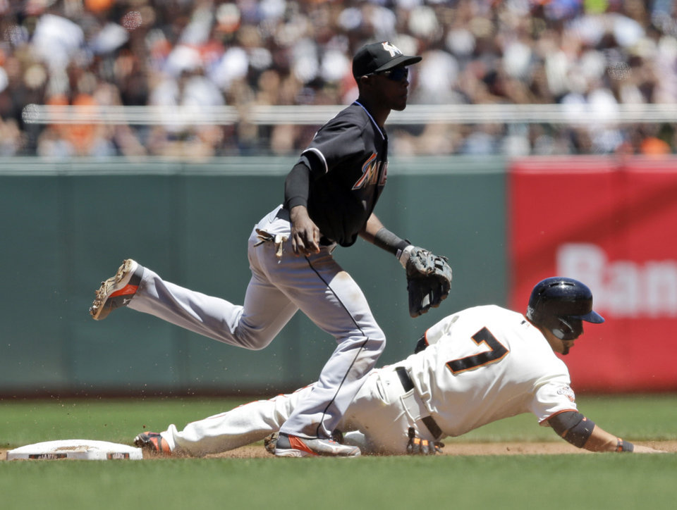 Photo - Miami Marlins shortstop Adeiny Hechavarria, left, turns a double play over San Francisco Giants' Gregor Blanco (7) on a ground ball from Marco Scutaro during the third inning of a baseball game on Saturday, June 22, 2013, in San Francisco. (AP Photo/Marcio Jose Sanchez)