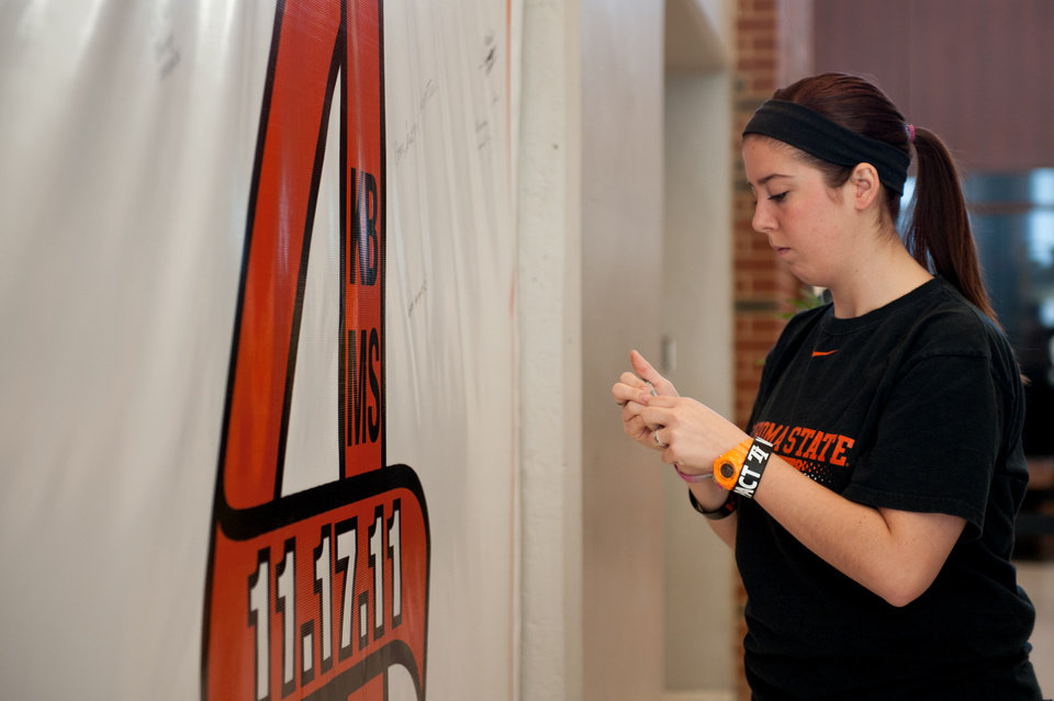 Taylor Miller writes on the Remember the 4 banner in Gallagher-Iba arena in Stillwater, Okla on Nov. 16, 2013. Oklahoma State University remembers the four members of the OSU women's basketball program on the one year anniversary of their accident. Photos by Mitchell Alcala for The Okahoman