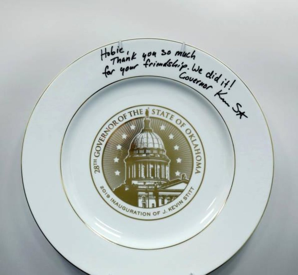 Photo -  This commemorative plate from Gov. Stitt's 2019 inauguration bears a personalized, hand-written note of gratitude from the governor. It was given to Hobie Higgins, chief engagement officer for Gateway First. The plate hangs in a place of prominence in Higgins' office. Photo taken Monday, July 15, 2019.   [Jim Beckel/The Oklahoman]