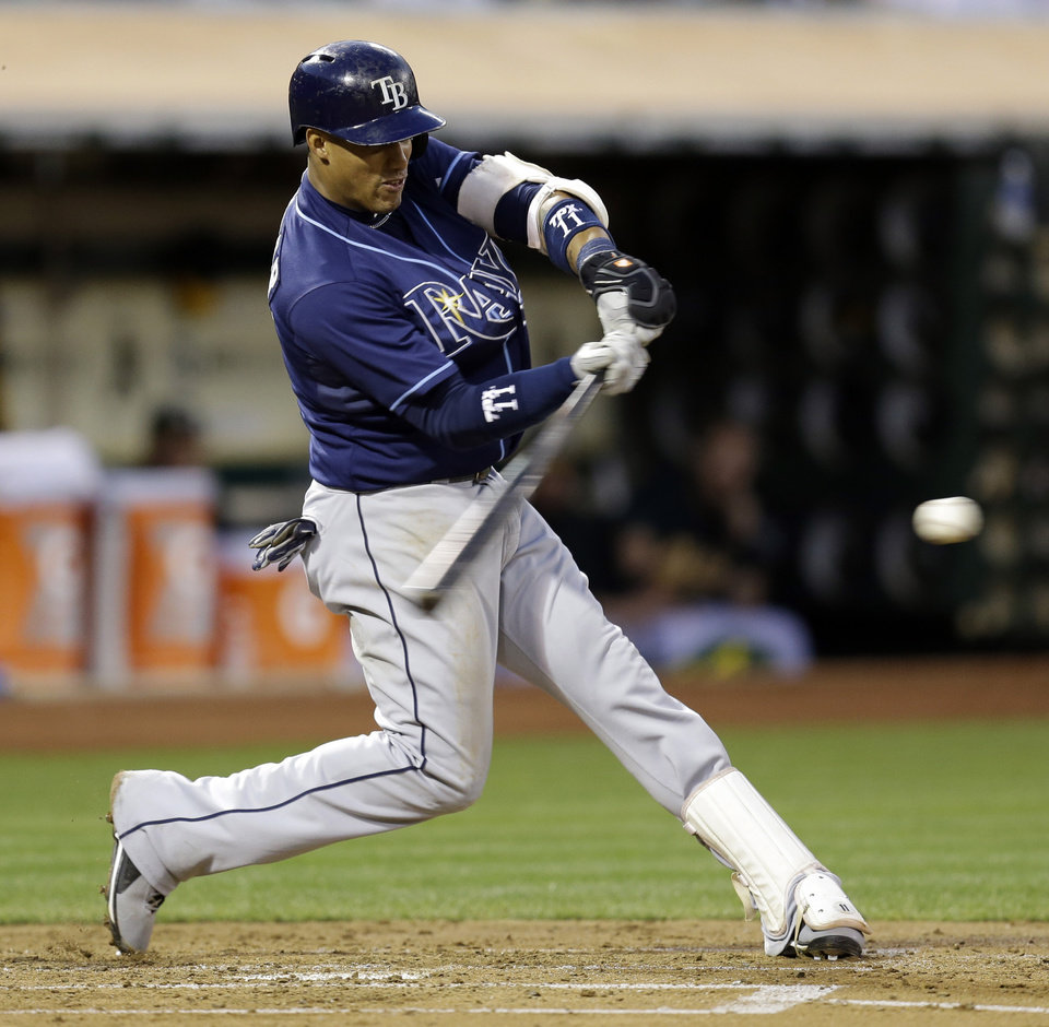 Photo - Tampa Bay Rays' Yunel Escobar connects for an RBI single off Oakland Athletics' Jarrod Parker in the second inning of a baseball game Friday, Aug. 30, 2013, in Oakland, Calif. (AP Photo/Ben Margot)