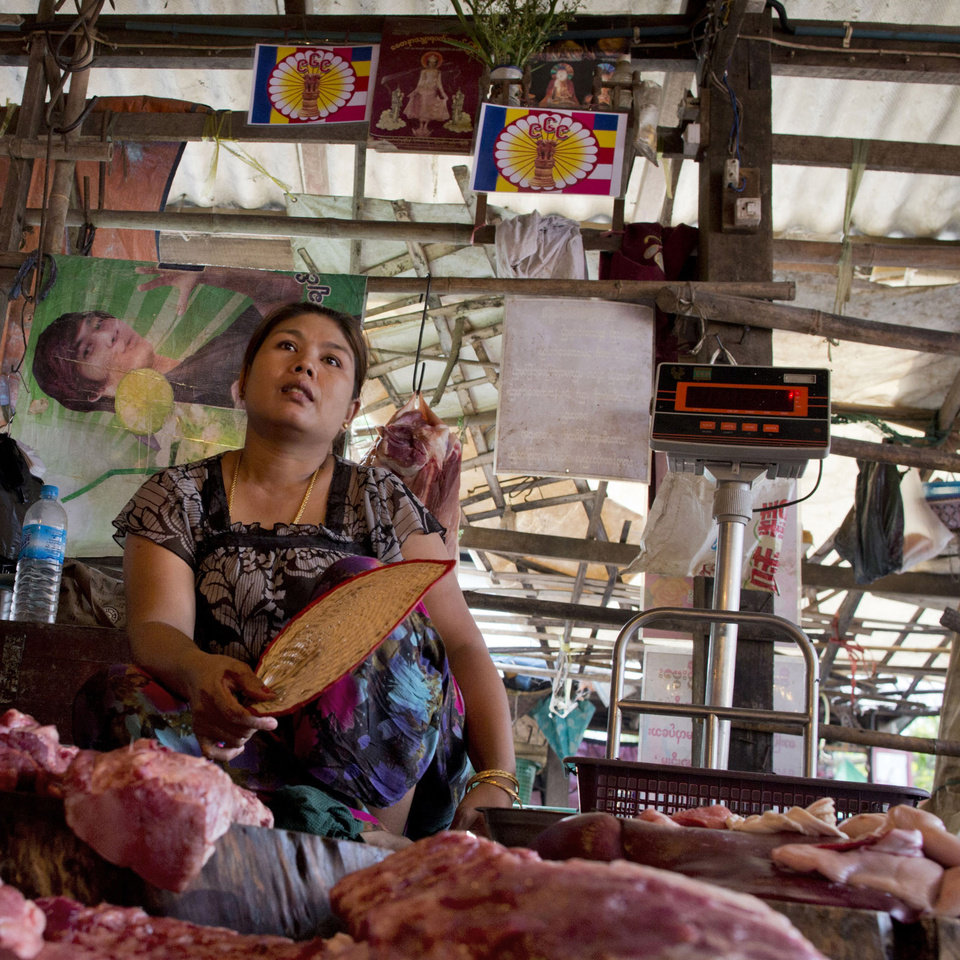 Photo - In this April 4, 2013 photo, Aye Aye Khine, right, sits beneath two 969 logos she hangs above her meat shop at the Kyimyindaing market in Yangon, Myanmar. She made the signs herself, copying them from the cover of a 969 DVD a friend gave her.
