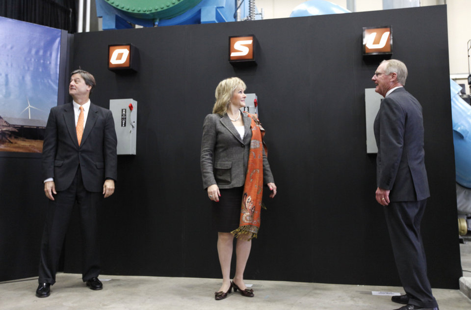 OG&E President Peter Delaney, left, Gov. Mary Fallin, and OSU President Burns Hargis flip symbolic switches to mark the completion of a 60-megawatt wind farm near Blackwell that will help supply power to the OSU campus in Stillwater. PHOTO BY PAUL HELLSTERN, THE OKLAHOMAN <strong>PAUL HELLSTERN - Oklahoman</strong>