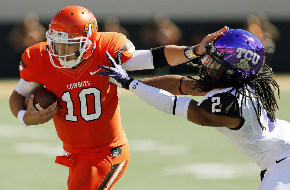 Oklahoma State\'s Clint Chelf (10) tries to break away from TCU\'s Jason Verrett (2) on a carry in the second quarter during a college football game between the Oklahoma State University Cowboys (OSU) and the Texas Christian University Horned Frogs (TCU) at Boone Pickens Stadium in Stillwater, Okla., Saturday, Oct. 19, 2013. Photo by Nate Billings, The Oklahoman