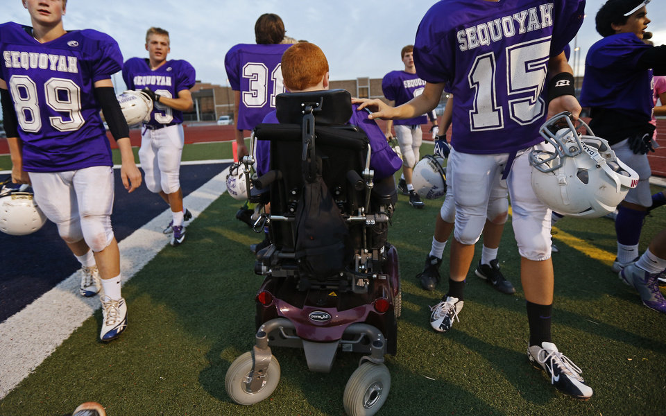 Photo - Members of the Sequoyah Middle School football team file by Keegan Erbst before a Sequoyah Middle School football game, Thursday, September 27, 2012. Keegan, who has muscular dystrophy and is confined to a wheelchair, got involved with the team after players Lucas Coker, Colton James, and Parker Tumleson, pushed suggested it to the coach.  Photo by Bryan Terry, The Oklahoman