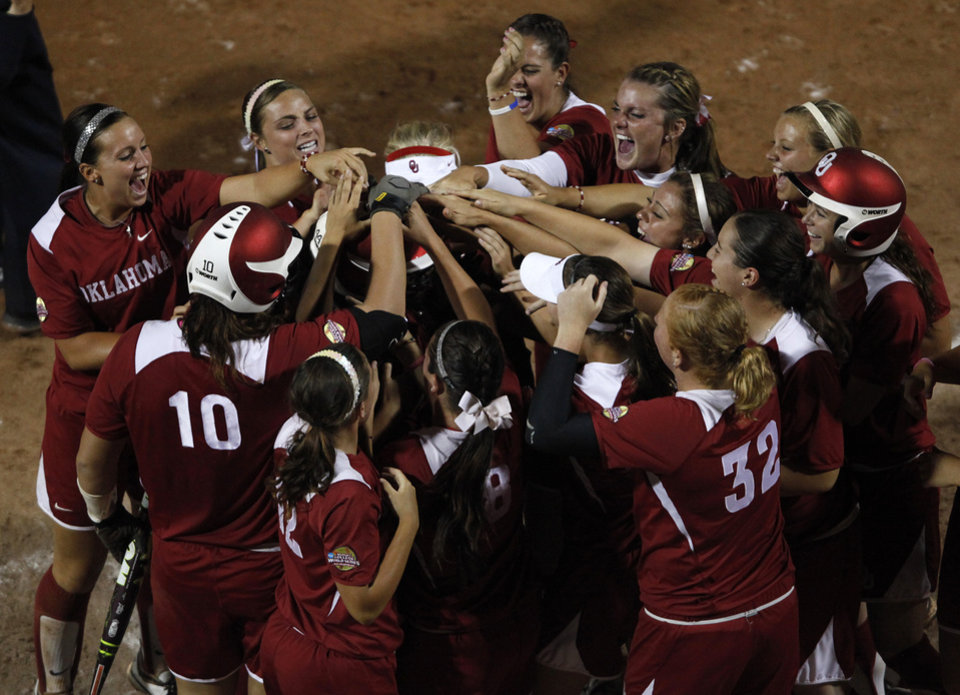 The Sooners welcome Lauren Chamberlain (44) to home base after she hit a home run during Game 3 of the Women's College World Series softball championship between OU and Alabama at ASA Hall of Fame Stadium in Oklahoma City, Wednesday, June 6, 2012.  Photo by Garett Fisbeck, The Oklahoman