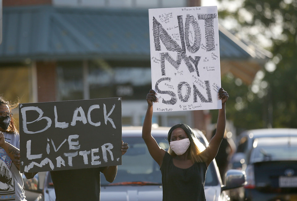 Photo - Protestors hold signs during a protest near the intersection of 23rd and Classen in Oklahoma City, Saturday, May 30, 2020. The protest was in response to the death of George Floyd. [Sarah Phipps/The Oklahoman]