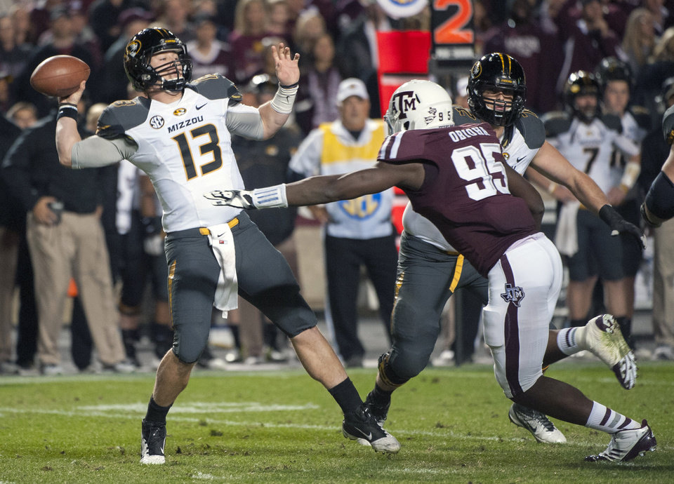 Missouri quarterback Corbin Berkstresser (13) passes under pressure by Texas A&M\'s Julien Obioha (95) during the second quarter of an NCAA college football game on Saturday, Nov. 24, 2012, in College Station, Texas. (AP Photo/Dave Einsel)