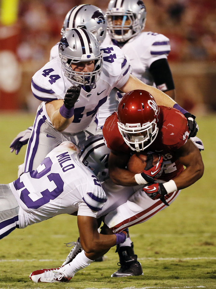 Brennan Clay (24) carries and is brought down by Jarard Milo (23) and Ryan Mueller (44) during the second half of a college football game where the University of Oklahoma Sooners (OU) lost 24-19 to the Kansas State University Wildcats (KSU) at Gaylord Family-Oklahoma Memorial Stadium, Saturday, September 22, 2012. Photo by Steve Sisney, The Oklahoman
