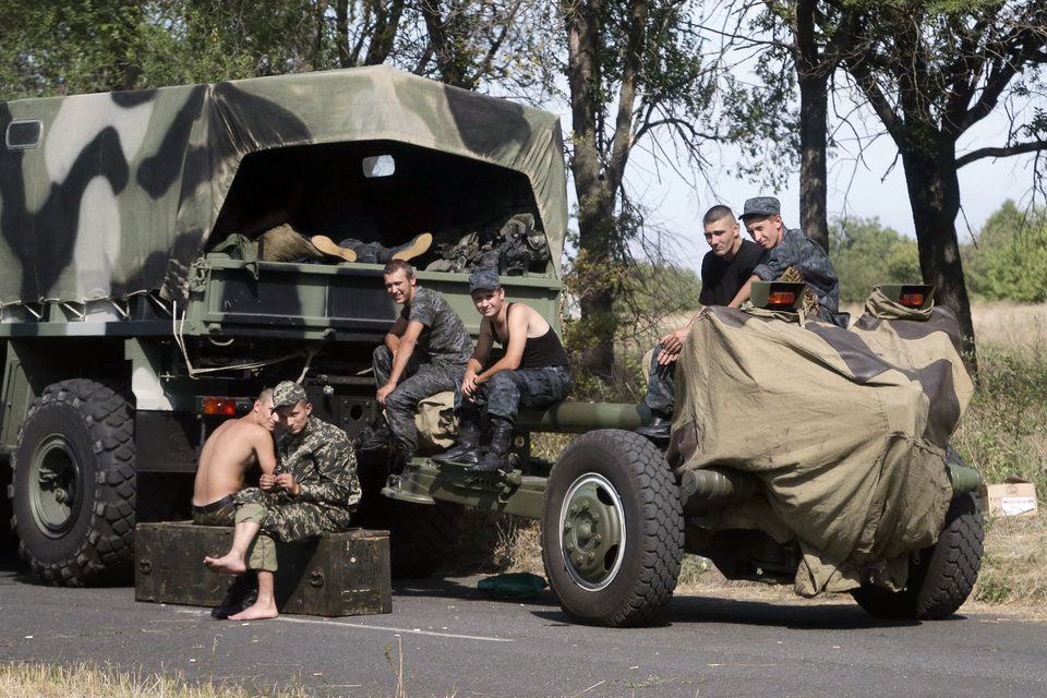 Photo - Ukrainian soldiers park their hardware on roadside as they wait for the start of the march into the town of Mariupol, eastern Ukraine, Wednesday, Aug. 27, 2014. Pro-Russian rebel forces entered a key town of Novoazovsk in southeastern Ukraine on Wednesday after three days of heavy shelling, the town's mayor said, capturing new territory far from most of their battles with government troops. (AP Photo/Sergei Grits)