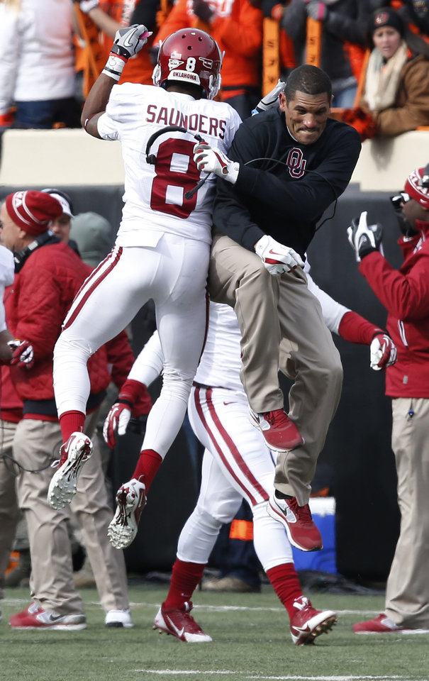 Oklahoma wide receiver Jalen Saunders (8) celebrates with assistant coach Jay Norvell, right, following his touchdown against Oklahoma State in the first quarter of an NCAA college football game in Stillwater, Okla., Saturday, Dec. 7, 2013. (AP Photo/Sue Ogrocki)