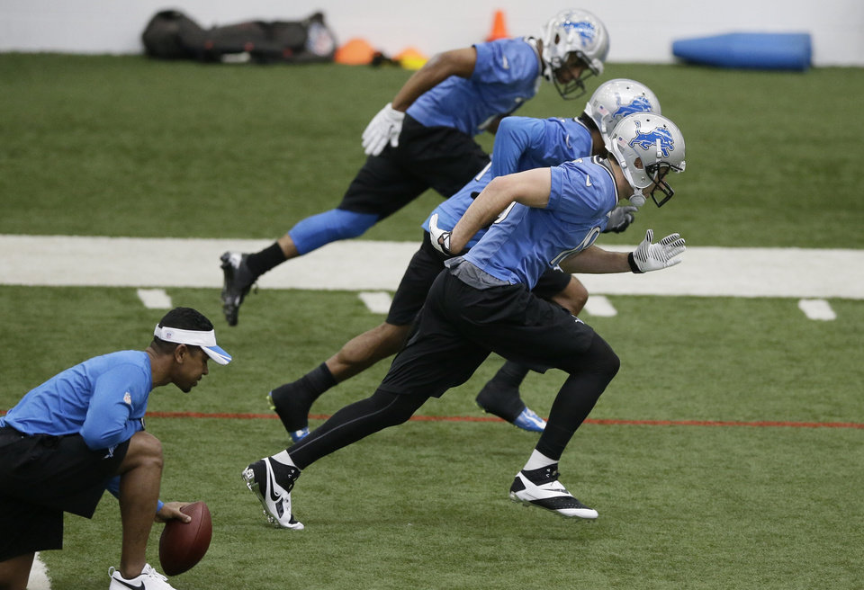 Photo - Detroit Lions receivers Golden Tate, top, Kevin Ogletree, center, and Kris Durham run through drills at the Lions training facility in Allen Park, Mich., Tuesday, April 22, 2014. (AP Photo/Carlos Osorio)
