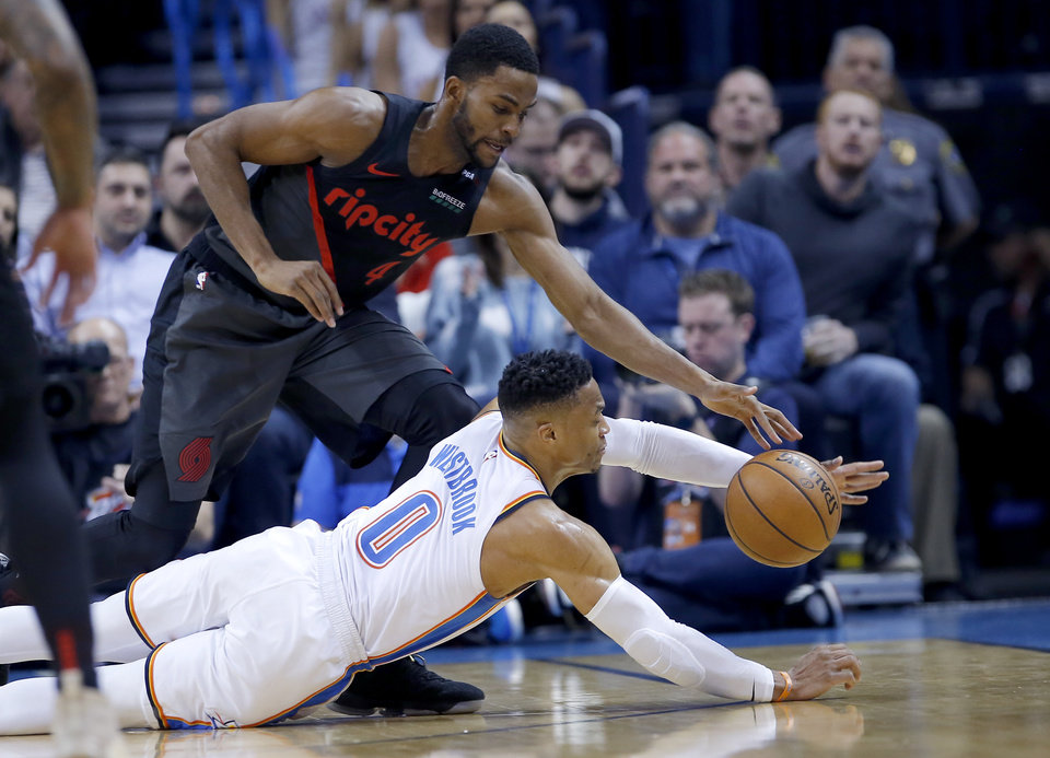 Photo - Oklahoma City's Russell Westbrook (0) dives for a loose ball as Portland's Maurice Harkless (4) defends during the NBA basketball game between the Oklahoma City Thunder and the Portland Trail Blazers at Chesapeake Energy Arena in Oklahoma City, Tuesday, Jan. 22, 2019. Photo by Sarah Phipps, The Oklahoman