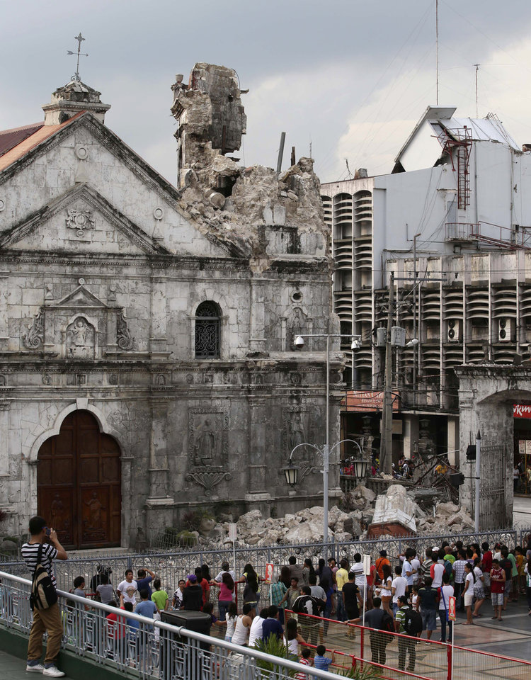 Photo - Residents look at the Basilica De Sto. Nino, or Basilica of the Holy Child, following a 7.2-magnitude earthquake that hit Cebu city in central Philippines Tuesday Oct. 15, 2013. The tremor collapsed buildings, cracked roads and toppled the bell tower of the Philippines' oldest church Tuesday morning, causing multiple deaths across the central region and sending terrified residents into deadly stampedes. (AP Photo/Bullit Marquez)