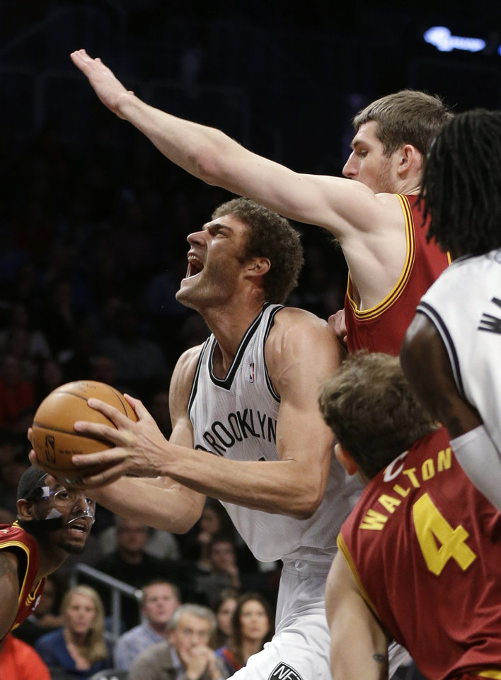 Photo - Brooklyn Nets' Brook Lopez drives past Cleveland Cavaliers' Tyler Zeller, top right, during the first half of an NBA basketball game Saturday, Dec. 29, 2012, in New York. (AP Photo/Frank Franklin II)