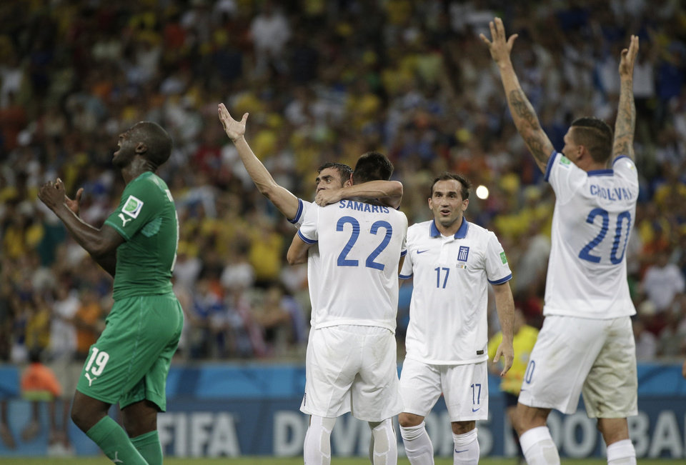 Photo - Ivory Coast's Yaya Toure reacts as Greek players celebrate after their 2-1 victory over Ivory Coast during the group C World Cup soccer match between Greece and Ivory Coast at the Arena Castelao in Fortaleza, Brazil, Tuesday, June 24, 2014. (AP Photo/Bernat Armangue)