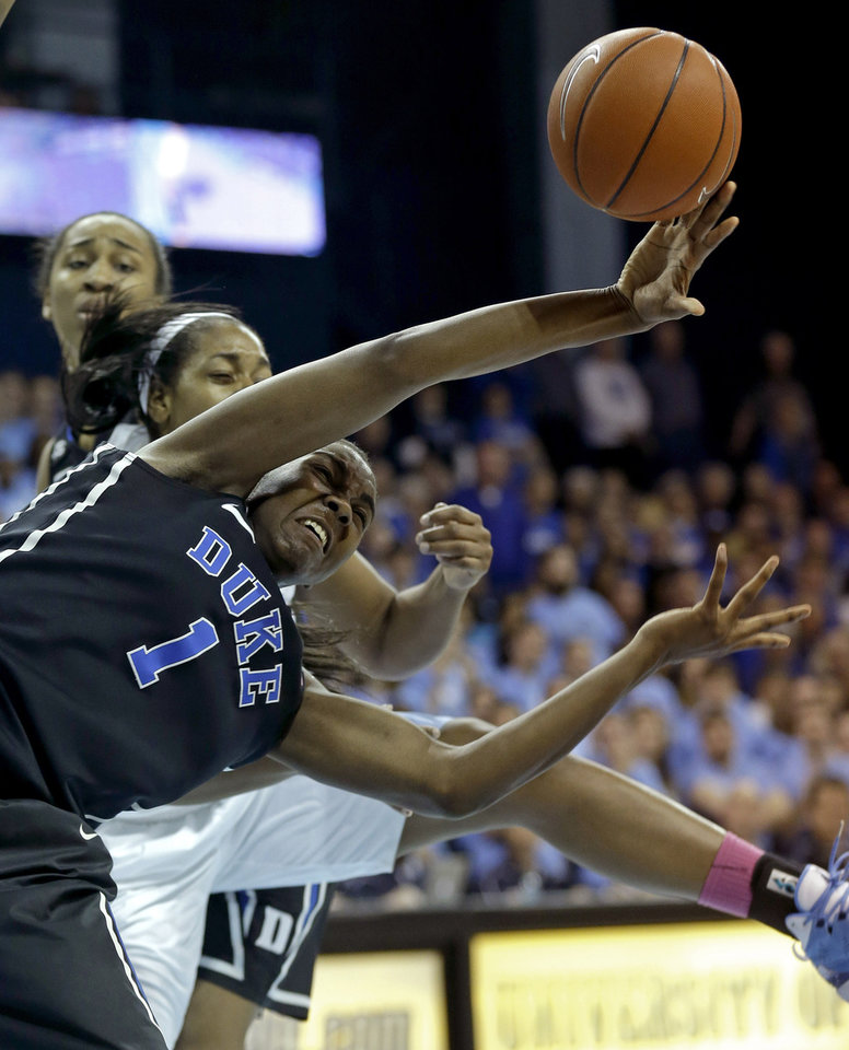 Photo - Duke's Elizabeth Williams (1) and North Carolina's Xylina McDaniel, rear, chase a loose ball during the first half of an NCAA college basketball game in Chapel Hill, N.C., Sunday, March 2, 2014. (AP Photo/Gerry Broome)