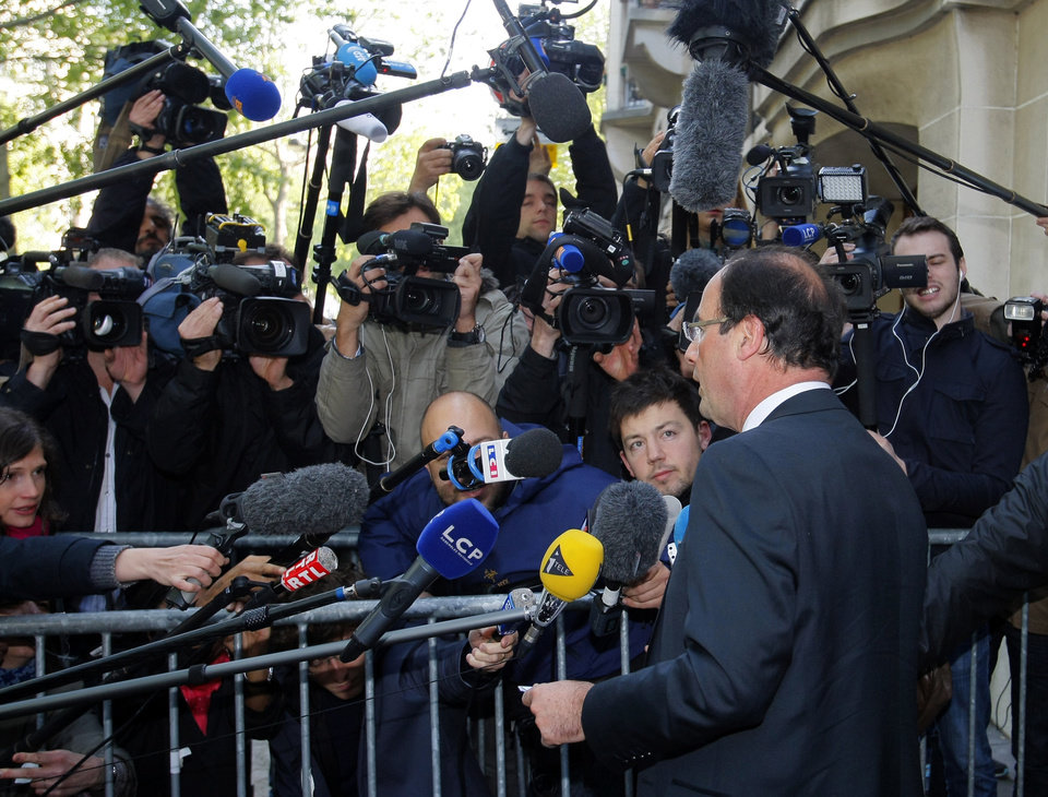 Photo -   President-elect Francois Hollande answers questions of journalists as he arrives at the Socialist Party headquarters in Paris Monday May 7, 2012. France handed the presidency to leftist Hollande, a champion of government stimulus programs who says the state should protect the downtrodden, a victory that could deal a death blow to the drive for austerity that has been the hallmark of Europe in recent years. (AP Photo/Michel Spingler)