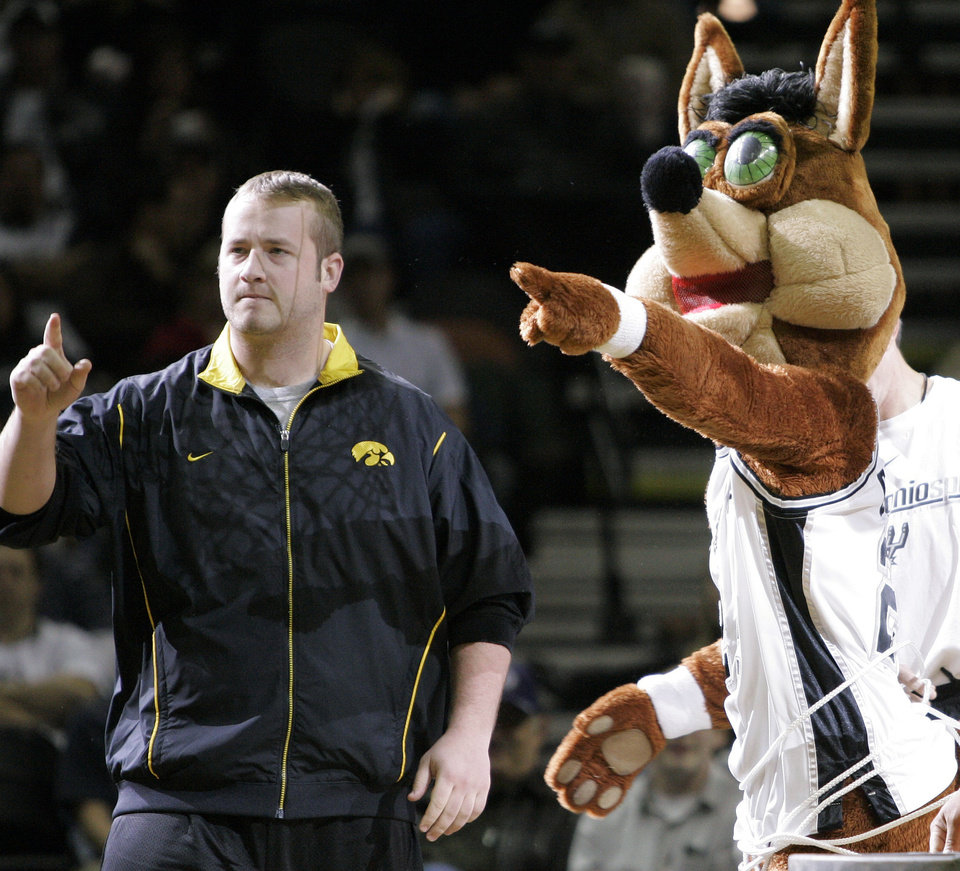 Photo - COYOTE: Iowa football player Bryan Ryther takes part in a skit with the San Antonio Spurs mascot during a timeout in an NBA basketball game against the Milwaukee Bucks, Tuesday, Dec. 26, 2006, in San Antonio. Iowa will face Texas in the Alamo Bowl on Saturday. (AP Photo/Eric Gay) ORG XMIT: SAA105