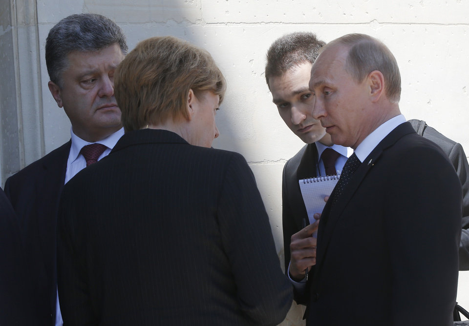 Photo - German Chancellor Angela Merkel, center, Russian President Vladimir Putin, right, and Ukrainian president-elect Petro Poroshenko, left, talk after a group photo as they take part in the 70th anniversary of D-Day in Benouville in Normandy, France, Friday, June 6, 2014. Man second right is unidentified. (AP Photo/Charles Dharapak)