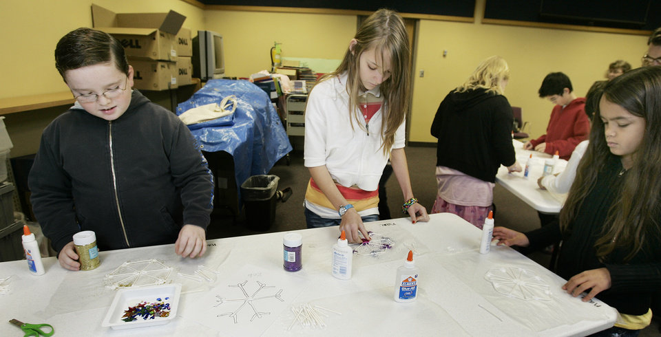 L to R Jerad Schragel, 10, Cheyenne Sewell, 11, Lexus Sanchez, 10, make snowflakes during crafts at the Norman Public Library Sat. Jan 10, 2009 in Norman, OK. BY JACONNA AGUIRRE, THE OKLAHOMAN